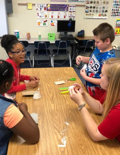 As a lover of STEM education, I enjoy spending time with students as a STEM Coach. Here I am in May 2019 with a group of students from McGee's Elementary School in Johnston County. We are designing a boat made out of cardboard and cups that can be powered by a rubber band!