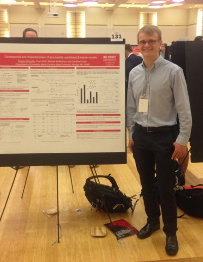 "In April 2019, I presented my research at the NC State Spring Undergraduate Research Symposium at Talley. Here I am next to my poster titled, ""Development and Characterization of Aza-peptide Substituted β-hairpin Models."""